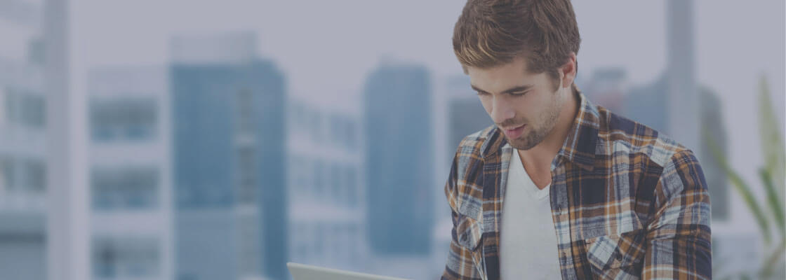 man using IoT device with tall buildings in background